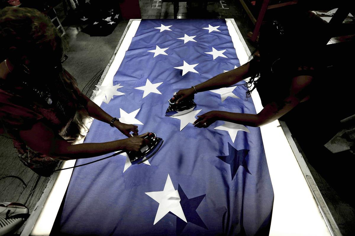 Employees Lottie Penick, left, and Melissa Hodnett iron stars onto a United States flag at Annin Flagmakers in South Boston, Va. July 6, 2016. (AP Photo/Gerry Broome)