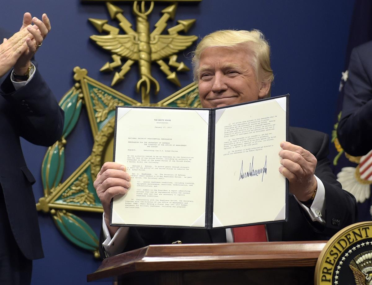 President Donald Trump shows his signature on an executive action on rebuilding the military during an event at the Pentagon in Washington, Friday, Jan. 27, 2017. (AP Photo/Susan Walsh)
