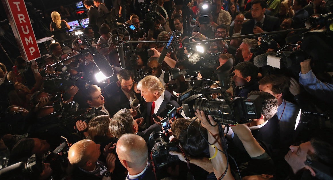 Then-candidate Donald Trump surrounded by reporters during the campaign (Politico)