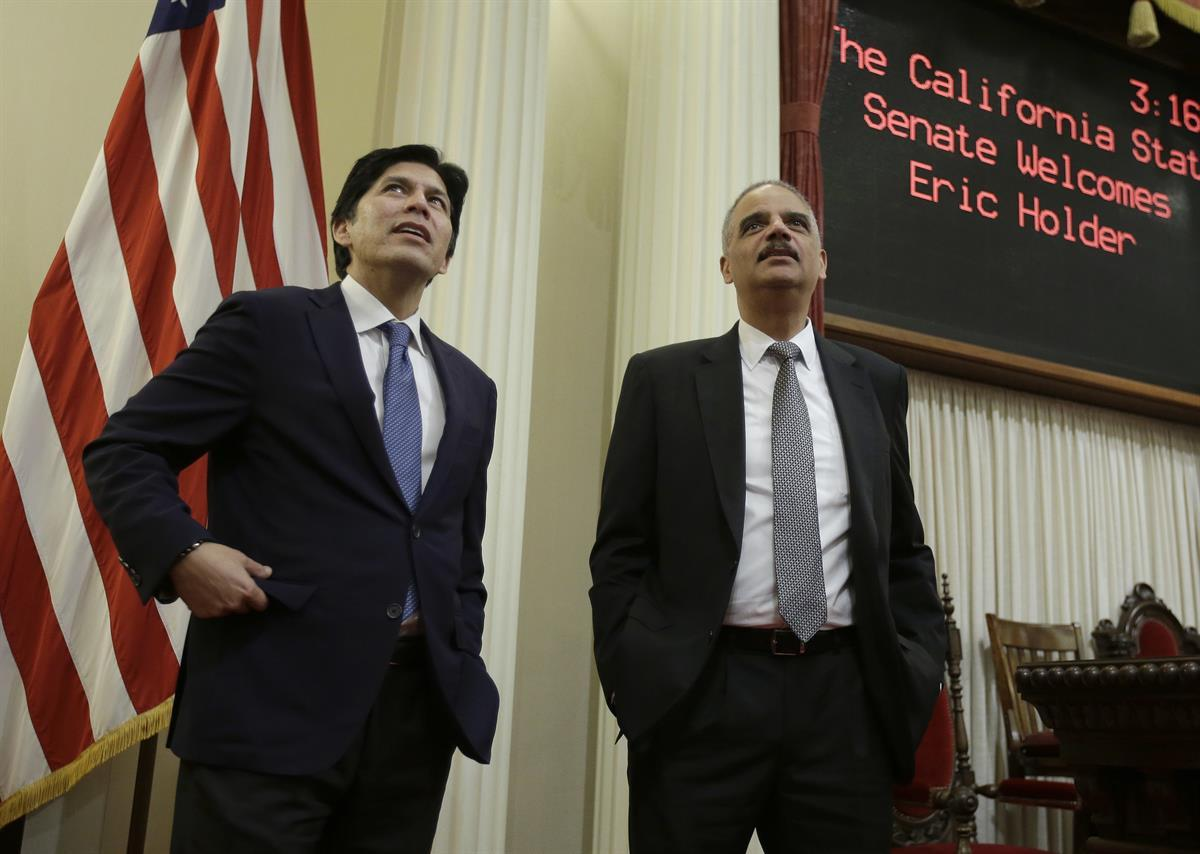 Former U.S. Attorney General Eric Holder, right, is given a tour of the state Senate chamber by Senate President Pro Tem Kevin de Leon, D-Los Angeles, Tuesday, Feb. 7, 2017, in Sacramento, Calif. (AP Photo/Rich Pedroncelli)