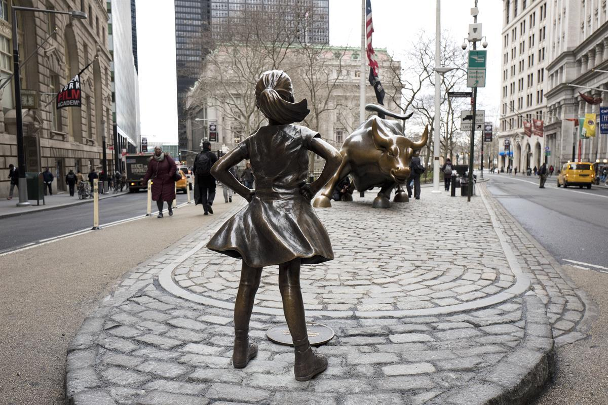 """The """"Fearless Girl"""" statue faces Wall Street's charging bull statue, Wednesday, March 8, 2017, in New York. An inscription at the base reads, """"Know the power of women in leadership. She makes a difference."""" (AP Photo/Mark Lennihan)"""