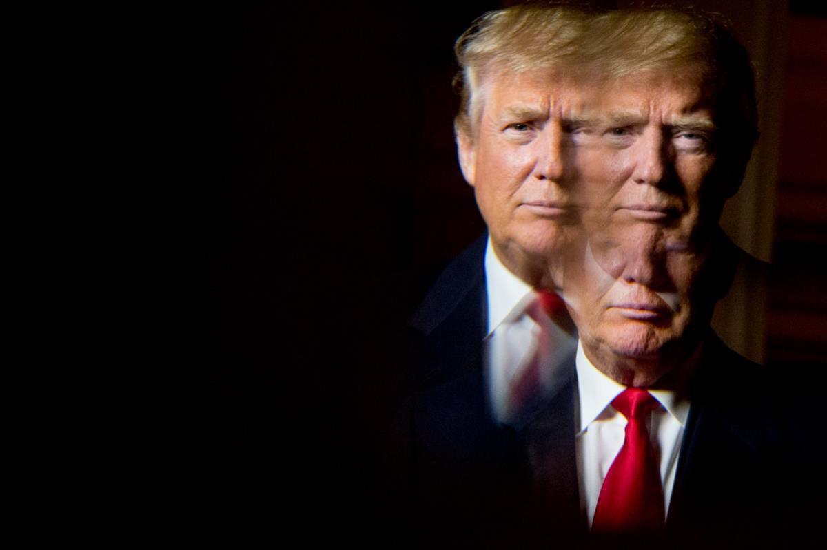Donald Trump, seen in reflection, poses for a portrait following an interview with the Associated Press at the Trump National Golf Club in Sterling, Va., Wednesday, Dec. 2, 2015 (AP Photo/Andrew Harnik)