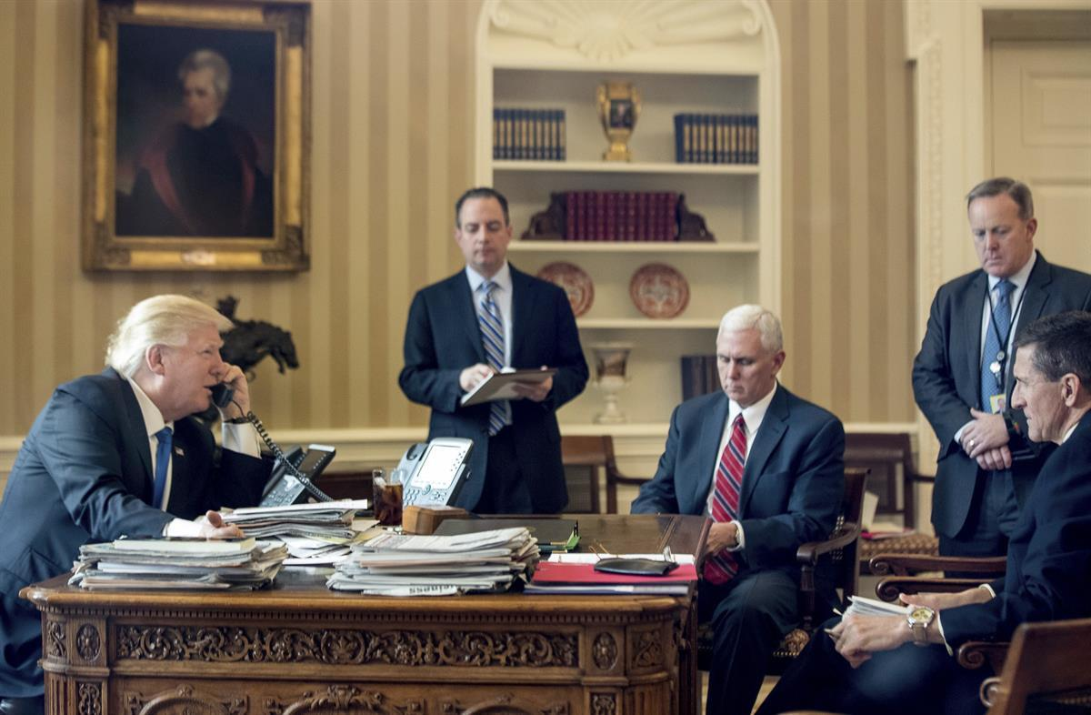 President Donald Trump, accompanied by, from second from left, Chief of Staff Reince Priebus, Vice President Mike Pence, White House press secretary Sean Spicer and former National Security Adviser Michael Flynn, speaks on the phone with Russian President Vladimir Putin, Saturday, Jan. 28, 2017, in the Oval Office at the White House in Washington. (AP Photo/Andrew Harnik)