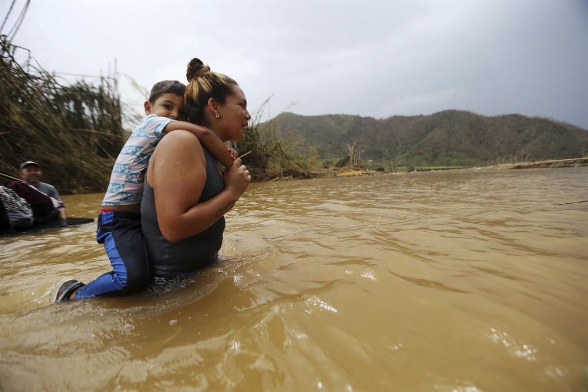 Marlene Ojeda carries her son Esaid Marrero through the Rio San Lorenzo de Morovis, after the bridge that crosses the river was swept away by Hurricane Maria, in Morovis, Puerto Rico, Wednesday, Sept. 27, 2017 (AP Photo/Gerald Herbert)