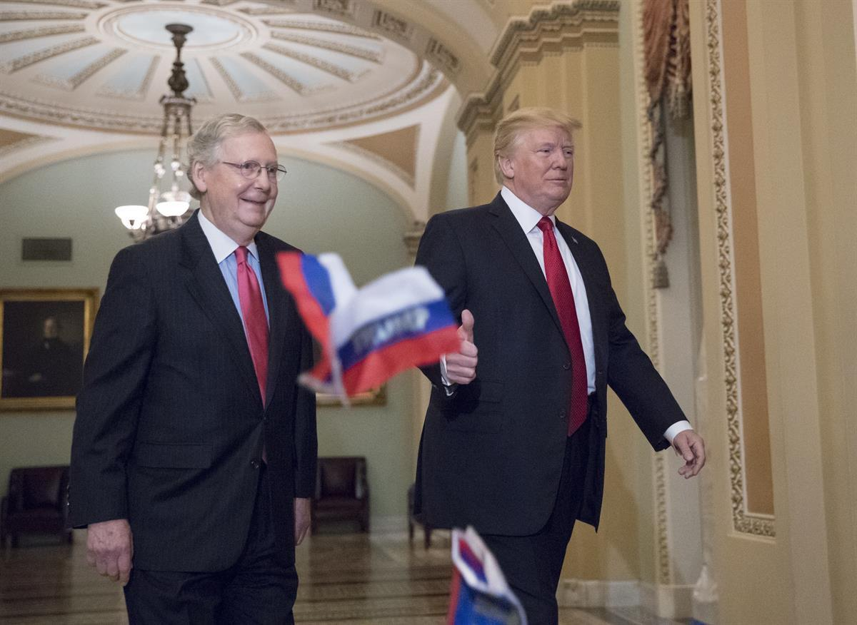 """Small Russian flags with the word """"Trump"""" written on them are thrown by a protester as President Donald Trump, escorted by Senate Majority Leader Mitch McConnell, R-Ky., arrives on Capitol Hill to have lunch with Senate Republicans and push for his tax reform agenda, in Washington—Tuesday, Oct. 24, 2017 (AP Photo/J. Scott Applewhite)"""