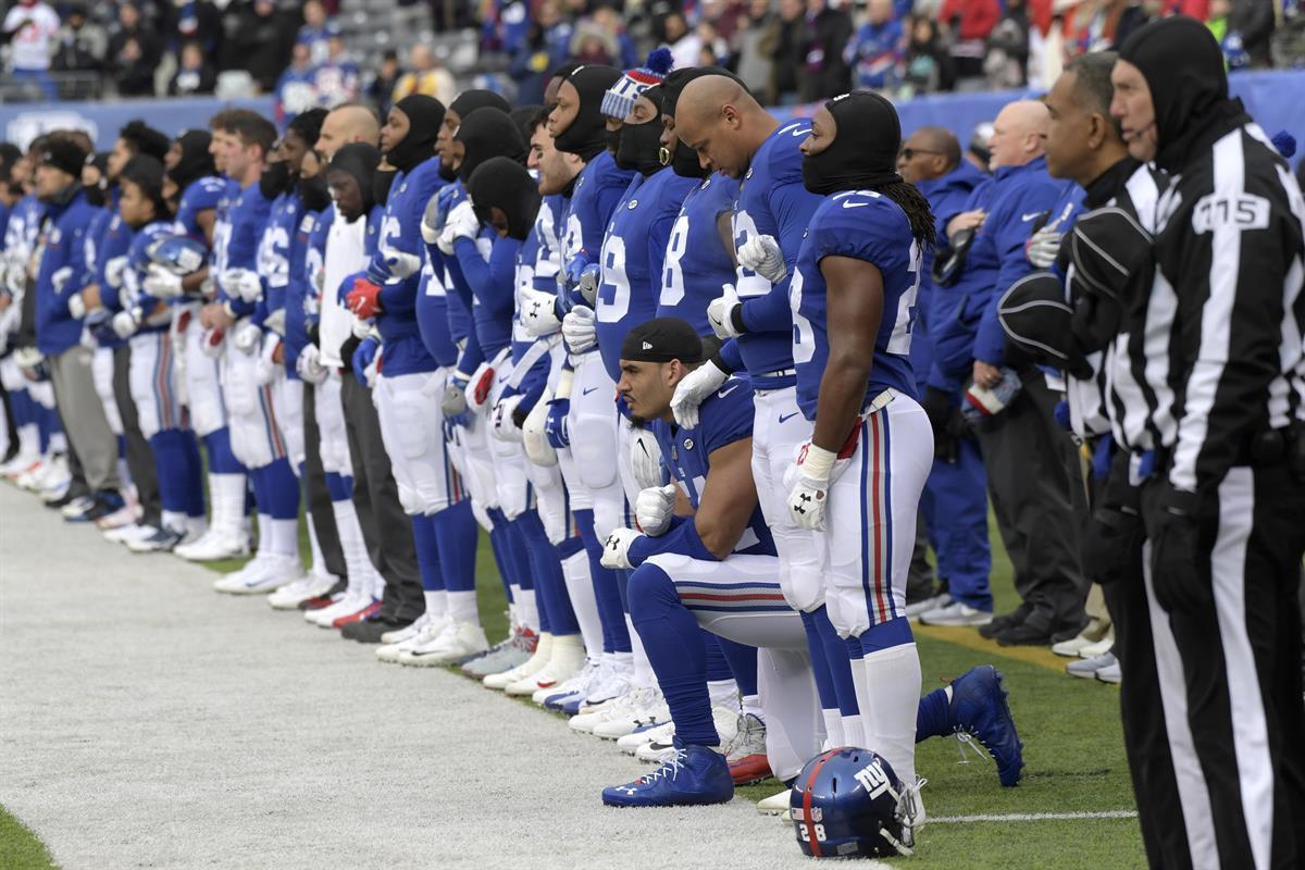 New York Giants defensive end Olivier Vernon kneels as the Giants stand for the national anthem before an NFL football game against the Washington Redskins Sunday, Dec. 31, 2017, in East Rutherford, N.J. (AP Photo/Bill Kostroun)