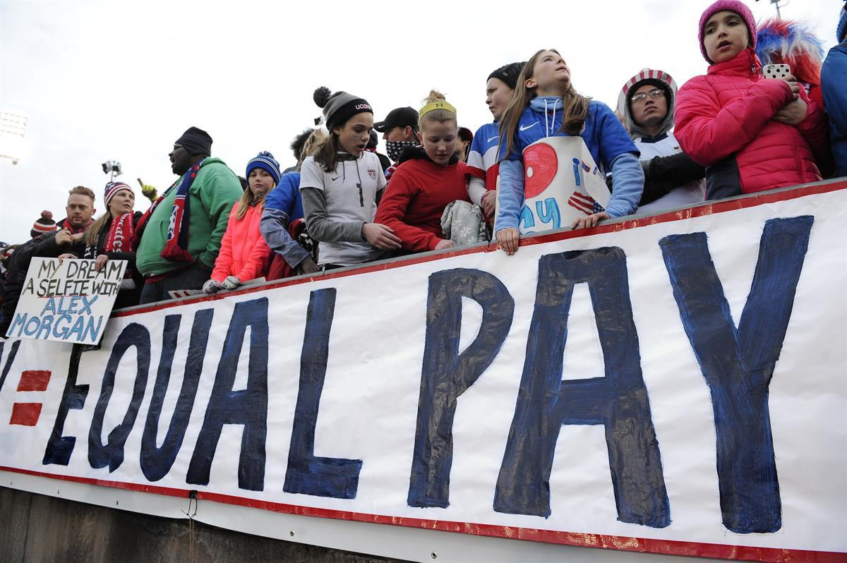 Fans stand behind a large sign for equal pay for the women's soccer team during an international friendly soccer match between the United States and Colombia at Pratt & Whitney Stadium at Rentschler Field in East Hartford, Conn.—April 6, 2016 (AP Photo/Jessica Hill,File)