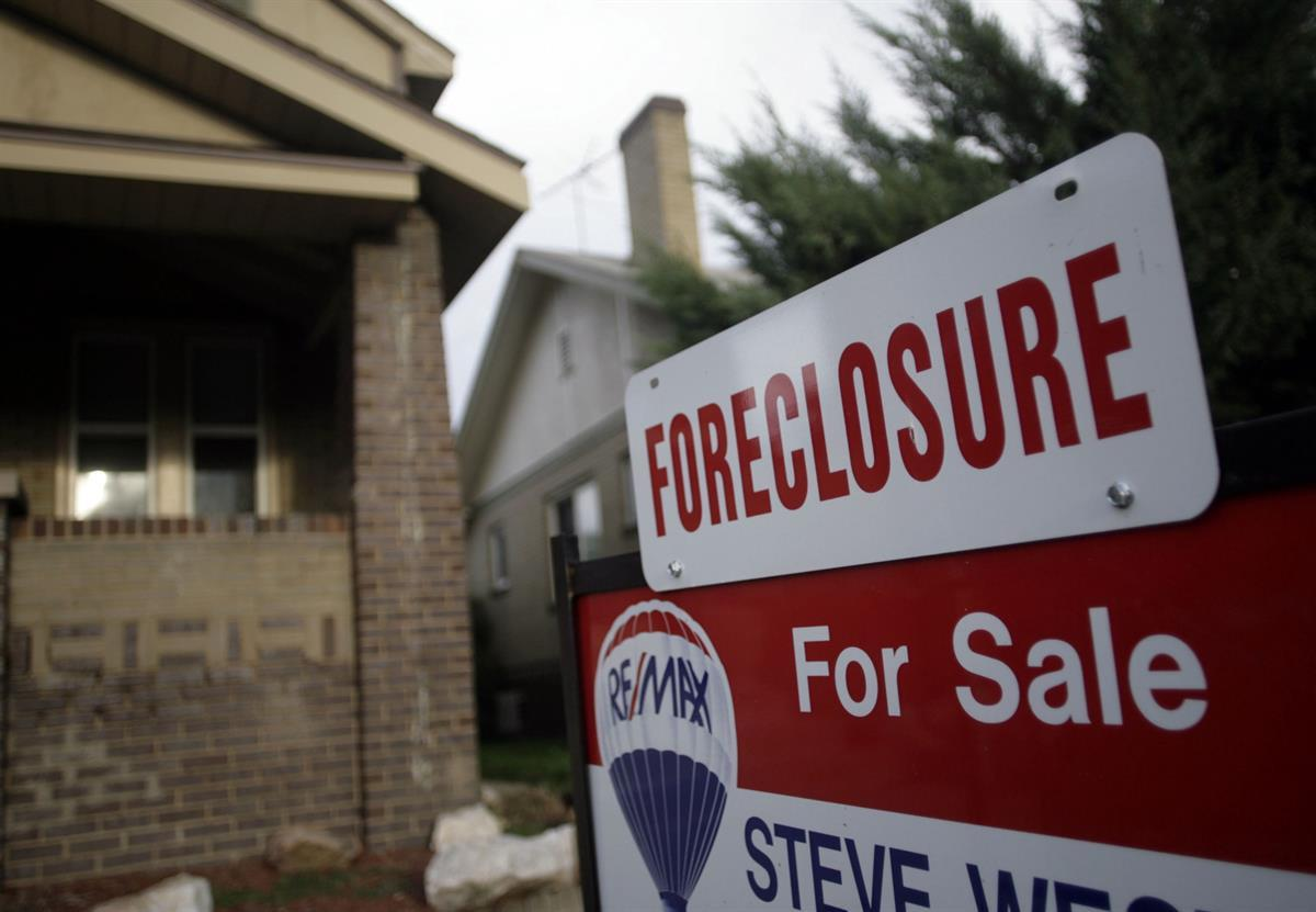 A foreclosure sign tops a sale sign outside an existing home on the market in northwest Denver—Aug. 29, 2007 (AP Photo/David Zalubowski, file)